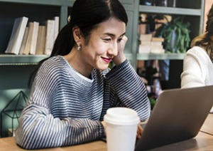 Asian woman in a cafe on her laptop