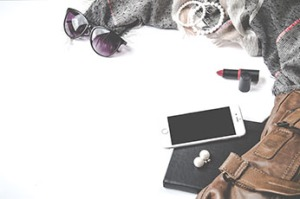 brown handbag with black diary and iphone, lipstick, jewellery and sunglasses