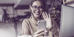 Grinsende Frau, die ihr Handy benutzt um mit Freunden zu telefonieren