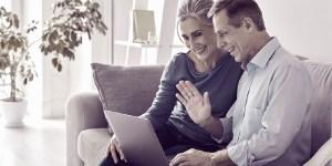 Mann und Frau lächelnd auf dem Sofa, winken dem Laptop