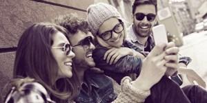 Viber blog hero - 4 Personen, die auf ein Smartphone gucken und lachen